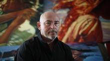 Artist Mark Heine sits in front of three of 34 oil paintings from his recent show in Vancouver, titled Child's Play, at his studio in Victoria on Wednesday. (CHAD HIPOLITO FOR THE GLOBE AND MAIL)