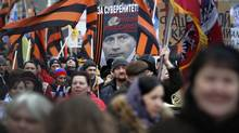 """Thousands of pro-Kremlin demonstrators holding Moscow and St. George flags and a poster depicting President Putin in a naval hat march in central Moscow, March 2, 2014. The poster reads : """"Sovereignty! Because I Love Russia! V. Putin"""" (Pavel Golovkin/AP)"""
