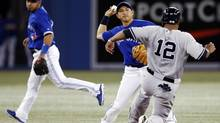 Toronto Blue Jays Munenori Kawasaki (C) turns a double play with teammate Maicer Izturis (L) over New York Yankees Vernon Wells during the fifth inning of their MLB American League baseball game in Toronto, April 20, 2013. (MARK BLINCH/REUTERS)