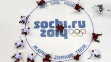 Russian men's hockey team players stretch at center ice during the team's first practice at the 2014 Sochi Winter Olympics (BRIAN SNYDER/REUTERS)