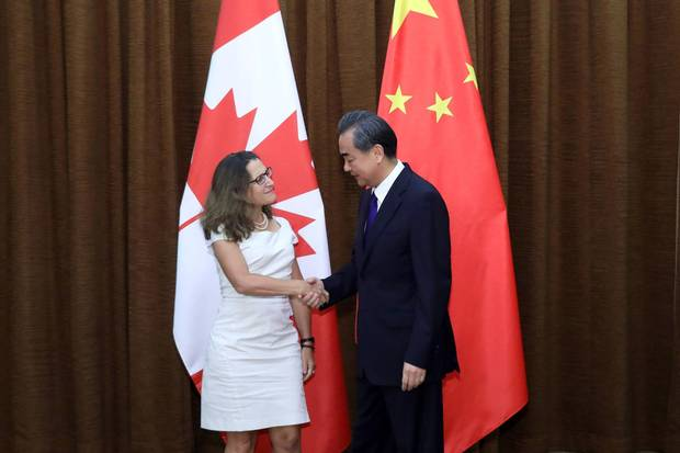 Canada's Foreign Minister Chrystia Freeland (L) shakes hands with her Chinese counterpart Wang Yi as she arrives for a meeting at the Ministry of Foreign Affairs in Beijing on August 9, 2017.