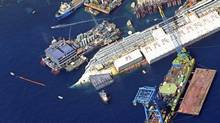 An aerial view shows the Costa Concordia as it lies on its side next to Giglio Island taken from an Italian navy helicopter August 26, 2013. The wrecked Costa Concordia cruise ship could be upright again next week, nearly two years after the liner capsized and killed at least 30 people off the Italian coast. The giant vessel, which has lain partly submerged in shallow waters off the Tuscan island of Giglio since the accident in January 2012, will be rolled off the seabed and onto underwater platforms. (ALESSANDRO BIANCHI/REUTERS)