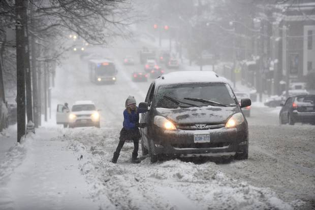 A young girl helps push a van as it slides on Avenue Road in Toronto on Dec. 11, 2014.