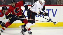 Anaheim Ducks' Corey Perry, right, gets tripped up by Calgary Flames' Cory Sarich (Jeff McIntosh/The Canadian Press)