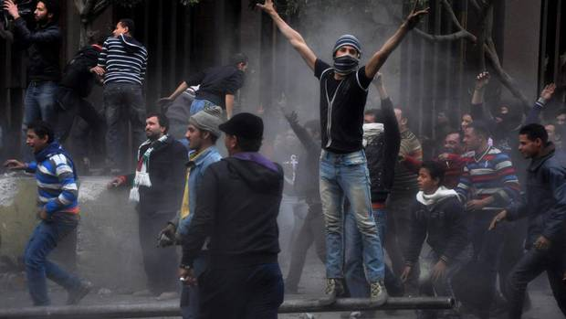 Egyptian protesters try to tear down a cement wall built to prevent them from reaching parliament near Tahrir Square, in Cairo, on Jan. 24, 2013. Egypt's black-clad riot police fired tear gas in fierce dawn clashes with dozens of protesters.