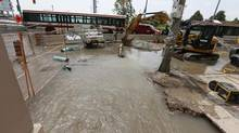 A water main rupture causes a flood at Queens Quay and Spadina Avenue in Toronto on July 10, 2013. (Gloria Nieto/The Globe and Mail)