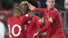 Canada's Simeon Jackson (L) and Kevin McKenna (R) celebrate with teammate Tosaint Ricketts after he scored on Cuba in the first half of their 2014 FIFA World Cup qualifying match in Toronto October 12, 2012. (FRED THORNHILL/REUTERS)