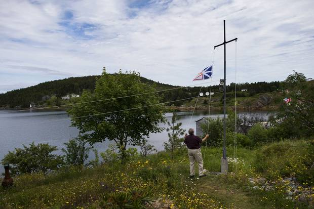 Ray Flynn raises Newfoundland's flag on his property in Little Bay Islands.