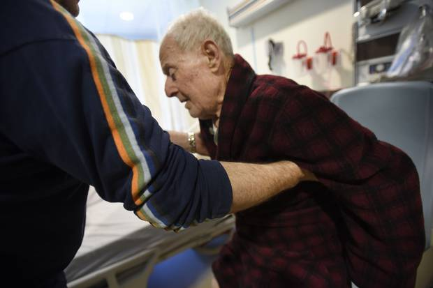Tom Spanidis, left, helps his father out of his chair. The younger Mr. Spanidis says that when he refused to take his father home, hospital officials promised to start charging him $1,100 a day to stay.