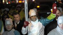 Akshay Kumar carries the Olympic Torch down Yonge Street in downtown Toronto in December. (Fred Lum/Fred Lum/The Globe and Mail)