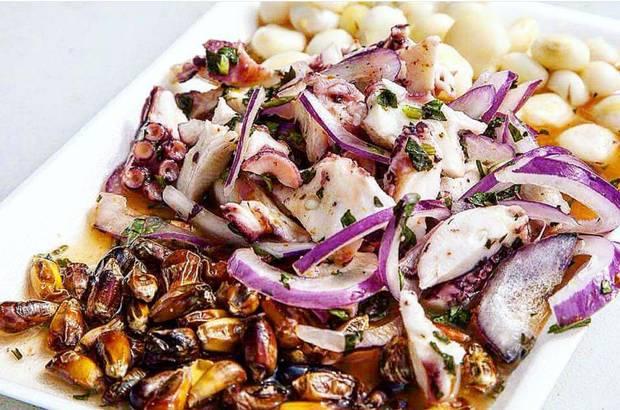 Ceviche de Pulpo features moroccan octopus, cuzco corn, chulpes, red onion, aji amarillo and leche de tigre.