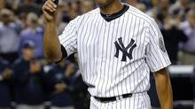 New York Yankees relief pitcher Mariano Rivera tips his cap to the crowd and the Tampa Bay Rays (rear) as they applaud him as he leaves the game in the ninth inning of their MLB American League game at Yankee Stadium in New York, September 26, 2013. It was Rivera's final appearance at the stadium as he is retiring at the end of the season. (RAY STUBBLEBINE/REUTERS)