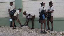 Students dust off their shoes in Port-au-Prince on Jan. 9, 2012. Schools that were open before the Haitian quake are functioning again. (SWOAN PARKER/REUTERS)