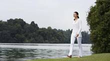 Woman walking by lake (Jupiterimages/Getty Images/Goodshoot RF)