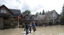 Residents walk through flood waters in Calgary on June 24, 2013. (Nathan Denette/THE CANADIAN PRESS)