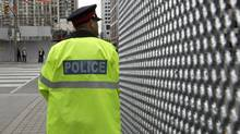 A police officer stands near security fence for the June 26-27 G20 Summit in Toronto June 14, 2010. (Reuters)