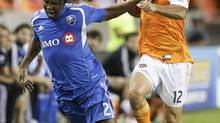 Montreal Impact defender Nelson Rivas (2) takes a shove from Houston Dynamo forward Will Bruin (12) in the second half during a knockout-round match in the MLS Cup playoffs, Thursday, Oct. 31, 2013, in Houston. Houston won 3-0. (Bob Levey/AP)