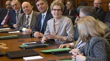 New Ontario Premier Kathleen Wynne sits with members of her cabinet for a photo opportunity prior to her first cabinet meeting at the Ontario Legislature in Toronto on Wednesday February 13, 2013. (Chris Young/THE CANADIAN PRESS)