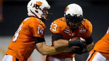 B.C. Lions' quarterback Travis Lulay, left, hands off to Andrew Harris during the first half of a CFL football game against the Saskatchewan Roughriders in Vancouver, B.C., on Saturday November 3, 2012. (DARRYL DYCK/THE CANADIAN PRESS)