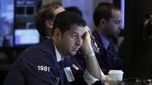 Trader Thomas Donato works on the floor of the New York Stock Exchange Tuesday, Oct. 23, 2012. Stocks fell sharply on Wall Street after 3M and DuPont slashed their earnings forecasts. (Richard Drew/The Associated Press)