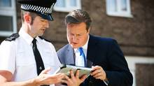 No, Britain's Prime Minister David Cameron is not scoping out some porn on the Internet (this is a file photo from his July visit to look at new community police crime prevention initiatives, including targeted CCTV and a new PC based mobile device, in Cheshunt, southern England). But he is proposing a sweeping filter to keep all that stuff away from his nation's shores. (Paul Rogers/Reuters)