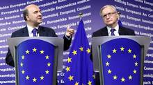 France's Minister of economy Pierre Moscovici, left, and European Economic and Monetary Affairs commissioner Olli Rehn hold a news conference after meeting at the Commission's headquarters in Brussels on Monday. (SEBASTIEN PIRLET/REUTERS)