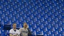 Toronto Blue Jays fans yell while sitting amongst empty seats at the Rogers Centre during baseball action between the Blue Jays and the Oakland Athletics in Toronto Wednesday, April 6, 2011. (Darren Calabrese/THE CANADIAN PRESS)