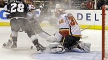 Calgary Flames goalie Joey MacDonald (35) defends the net as Los Angeles Kings center Jarret Stoll (28) attacks in the second period of an NHL hockey game in Los Angeles, Monday, March 11, 2013. (Reed Saxon/AP)