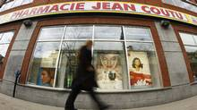 A pedestrian walks past a Jean Coutu pharmacy in downtown Montreal, April 28, 2010. (SHAUN BEST/REUTERS)