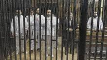 Ousted former Egyptian president Mohammed Morsi, second from right, stands with other senior figures of the Muslim Brotherhood on the first day of his trial in Cairo, November 4, 2013. (REUTERS)