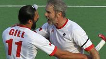 Canada's Rob Short (R) celebrates with teammate Jagdish Gill as Philip Wright (L) watches after a goal against France during their London 2012 Olympic Games men's field hockey qualifying match in New Delhi February 24, 2012. REUTERS/B Mathur (B Mathur/Reuters)