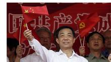 Bo Xilai waves a Chinese national flag during the opening ceremony of a revolutionary song singing concert at Chongqing Olympic Sports Centre in Chongqing municipality in this June 29, 2011, file photo. (JASON LEE/REUTERS)
