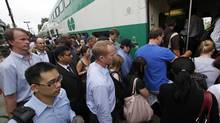 GO Transit passengers rush to catch an eastbound train at the Long Branch GO Station in Etobicoke on July 9, 2013. Shuttle buses were in service because of flooding on the tracks west of Long Branch following a massive rain storm Monday night. (Deborah Baic/The Globe and Mail)