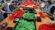 Labourers work toy factory in China's Guangdong province, in this file photo. China, until recently, had made strides in narrowing its current-account surplus. But now a wider Chinese trade surplus, and a U.S. trade deficit that grew 14 per cent in March, are replicating the imbalanced global economy that was too weak to withstand the ripple effects of the U.S. subprime-mortgage collapse. (ALY SONG/REUTERS)