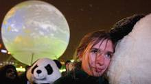 A woman cuddles a protester dressed as panda at an evening climate demonstration in Copenhagen. (Jeff J Mitchell/2009 Getty Images)