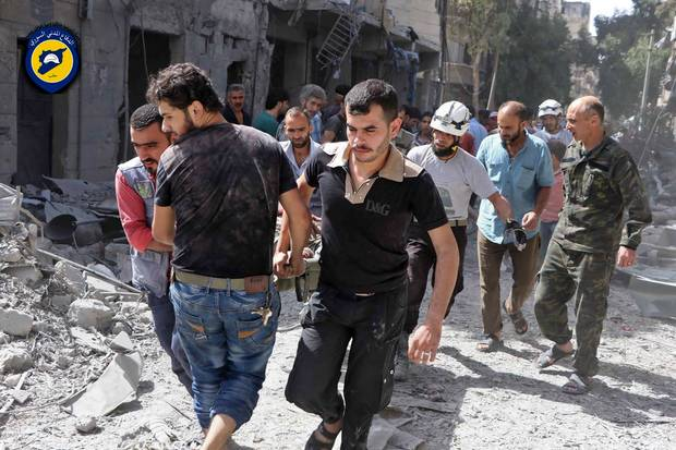 In this photo provided by the Syrian Civil Defense White Helmets, rescue workers work the site of airstrikes in al-Mashhad neighborhood in the rebel-held part of eastern Aleppo, on Sept. 21, 2016.