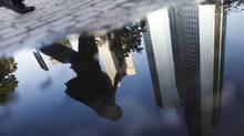 A July 12, 2011 file photo shows the headquarters of Deutsche Bank reflected in a puddle in Frankfurt. The bank disputes U.S. allegations that its traders manipulated the energy market. (ALEX DOMANSKI/REUTERS)