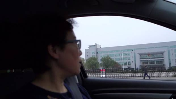 Jean Zou drives past the cigarette factory where her husband worked.