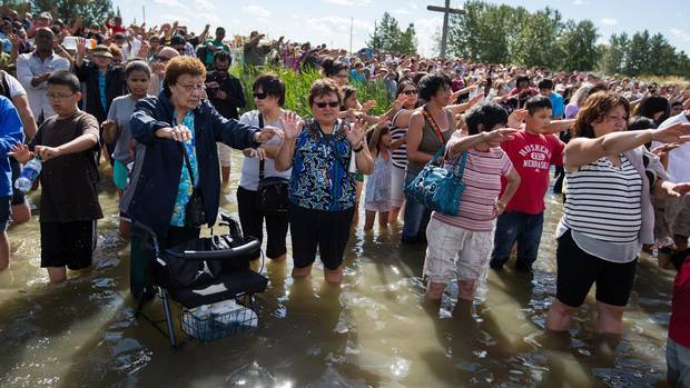Hundreds of believers bless the lake in a ceremony at Lac Ste Anne, Alberta on Sunday, July 19, 2015. Before Catholic missionaries arrived in the 1800's, Nakota First Nations called the lake Wakamne, or God's Lake, and First Nations people from all over North America came to pray and bathe in the healing water.