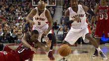 Miami Heat forward Chris Bosh (left) battles for a loose ball with Toronto Raptors guards John Lucas III (5) and Terrence Ross (31) during first half NBA action in Toronto on Sunday February 3, 2013. (Frank Gunn/THE CANADIAN PRESS)