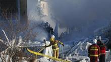 Firefighters and investigators look over the scene of a fire at a senior residence home in L'Isle Verte, Que., on Jan. 23, 2014. (CHRISTINNE MUSCHI FOR THE GLOBE AND MAIL)