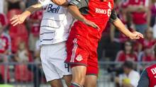 Toronto FC's Danny Koevermans fights for the ball with Vancouver Whitecaps FC's Alain Rochat (FRED THORNHILL/REUTERS)