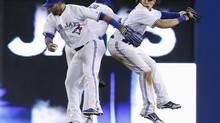 Toronto Blue Jays' Jose Bautista, Emilio Bonifacio and Colby Rasmus celebrate