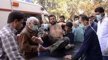 Residents and medics transport a Syrian Army soldier, wounded in what they said was a chemical weapon attack near Aleppo, to a hospital on March 19, 2013. (George Ourfalian/Reuters)