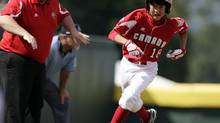 Vancouver, British Columbia, baserunner Ryan Mutsuda rounds third and heads home during Little League World Series pool play, Tuesday, Aug. 25, 2009, in South Williamsport, Pa. At left is manager Manager Vito Bordignon. (Carolyn Kaster/AP)