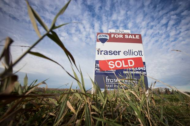 A for-sale sign stands on fallow farmland in Delta, B.C.