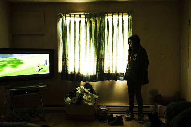 Home from school, Marleah looks at the television her father, James Trout, is watching. Mr. Trout, a residential school survivor, has tried to shield Marleah as much as possible, sharing little about his difficult journey to graduating high school.