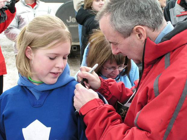 Ron MacLean of CBC's Hockey Night in Canada signs a young fans jersey in Shaunavon Saskatchewan as they get ready for CBC's Hockey Day in Canada broadcast.