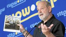 CUPW National President and Chief Negotiator Denis Lemelin holds up a picture of mail sitting at a Canada Post facility as he speaks with the media in Ottawa, Monday June 13, 2011. (THE CANADIAN PRESS/Adrian Wyld/THE CANADIAN PRESS/Adrian Wyld)
