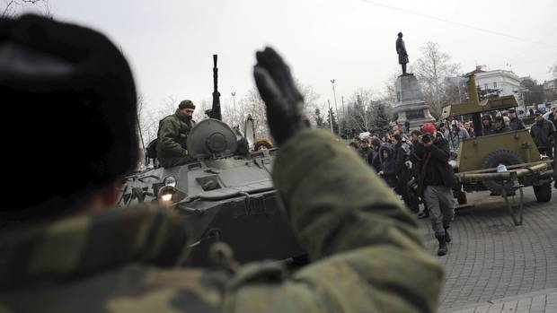 A Russian Army officer helps an armored personnel carrier drive on a street in Sevastopol, Ukraine's Black Sea port, on Feb. 25, 2014.